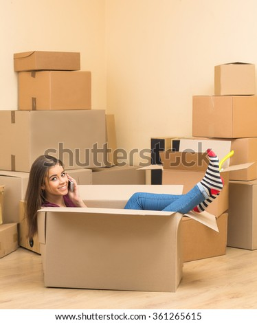 Happy woman sitting in a box in new apartment - stock photo