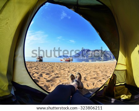 Happy woman sitting in a tent ,view of mountains ,sky and sea.Olympos Beach. Cirali, Turkey - stock photo