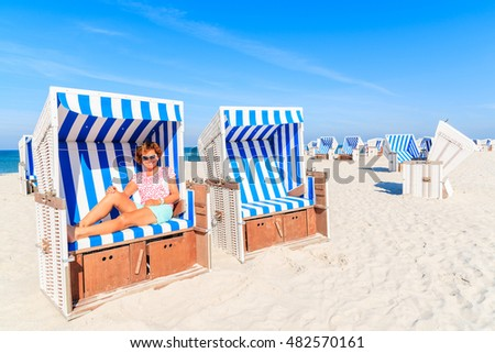 Happy woman sitting in beach chair and enjoying summer time, Kampen, Sylt island, Germany