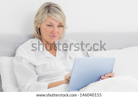 Happy woman sitting in bed using tablet pc at home in bedroom - stock photo
