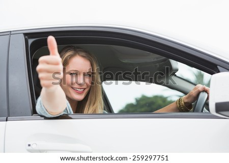 Happy woman sitting in drivers seat thumb up in her car - stock photo