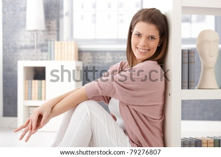 Happy woman sitting in smart living room at bookshelf, smiling at camera.? - stock photo
