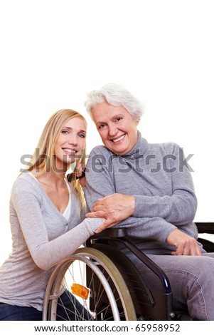 Happy woman sitting in wheelchair with young nurse to her side - stock photo
