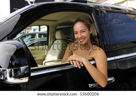 happy woman sitting inside of her new expensive 4x4 off-road vehicle - stock photo