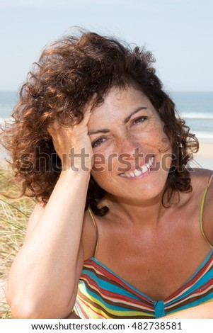 Happy woman sitting on beach and looking on copy space