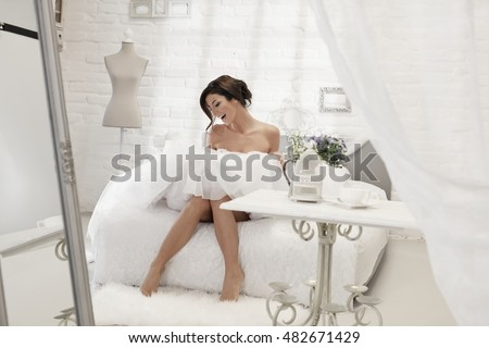 Happy woman sitting on bed in white wedding dress, having fun.