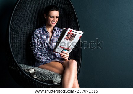 Happy woman sitting on bubble chair and reading magazine - stock photo