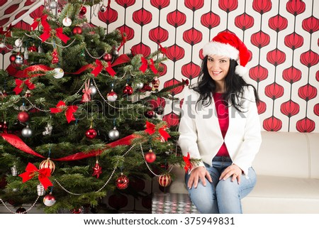 Happy woman sitting on couch in home near natural Chrismas tree with decorations
