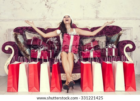 Happy woman sitting on couch with presents christmas time