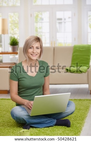 Happy woman sitting on floor at home in living room using laptop computer, looking at camera. - stock photo