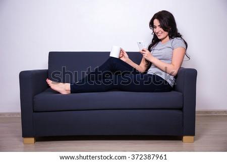 happy woman sitting on sofa with mobile phone and mug of tea or coffee - stock photo