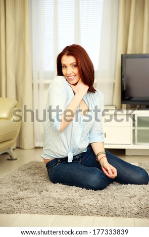 Happy woman sitting on the carpet at home - stock photo