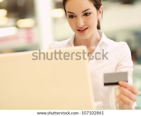 Happy woman sitting on the desk and shopping online isolated on white background - stock photo