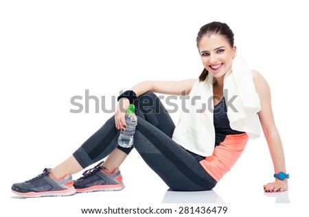 Happy woman sitting on the floor with bottle of water and towel isolated on a white background. Looking at camera - stock photo
