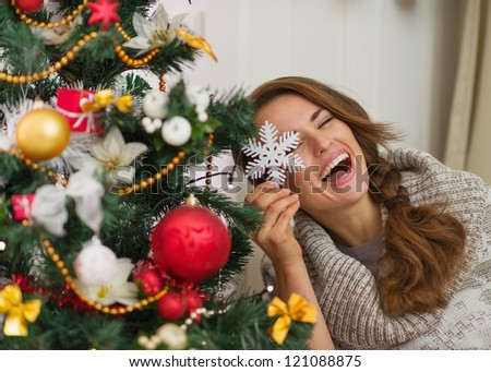 Happy woman sitting playing with Christmas tree decoration - stock photo