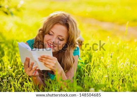 happy woman sitting reading book outdoors - stock photo