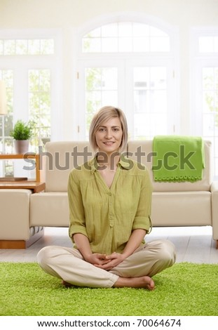 Happy  woman sitting with legs crossed on living room floor, looking at camera.? - stock photo