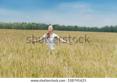 Happy woman smiles in a meadow - stock photo