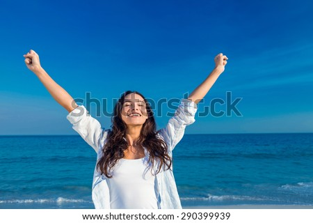 Happy woman smiling at the beach on a sunny day - stock photo