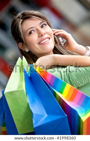 happy woman smiling on the phone with shopping bags