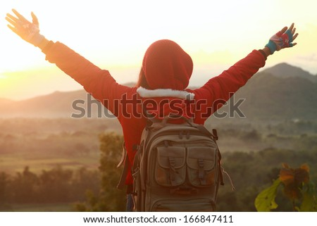 Happy woman spreading hands standing look the sunrise. Mountain hiking - stock photo
