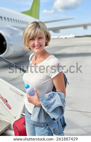 Happy woman standing at plane ladder going to board, outdoors, airport - stock photo