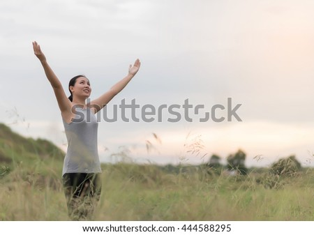 happy woman standing at the green field