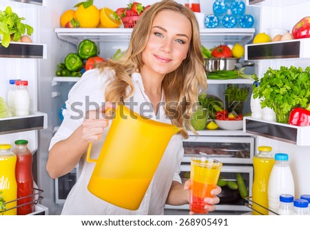 Happy woman standing near open refrigerator full of fresh fruits and vegetables and pouring juice in glass, healthy eating concept - stock photo