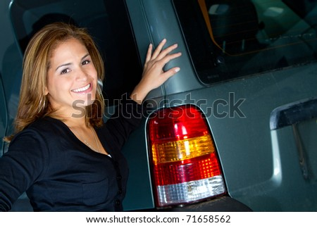 Happy woman standing next to her car - stock photo
