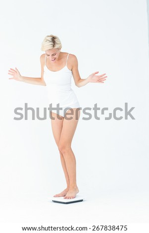 Happy woman standing on a scales on white background - stock photo