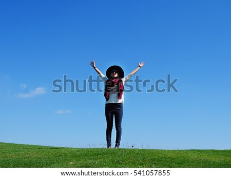 Happy woman standing on green field against blue sky. Inspiration for freedom concept. Copy space.