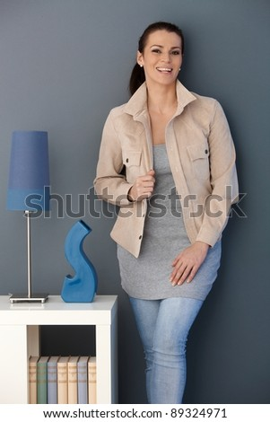 Happy woman standing posing in stylish living room, looking at camera.? - stock photo