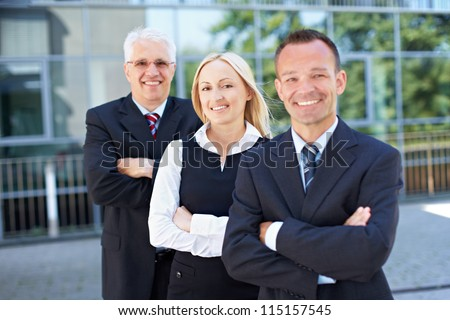 Happy woman standing with arms crossed in a business team - stock photo