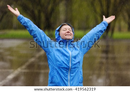 Happy woman standing with arms outstretched in rain - stock photo