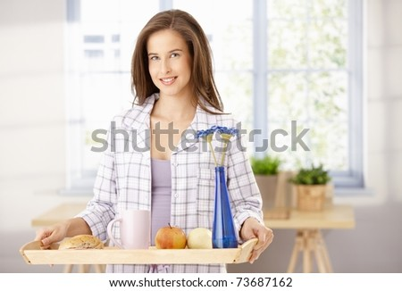 Happy woman standing with breakfast tray in living room, smiling at camera.?