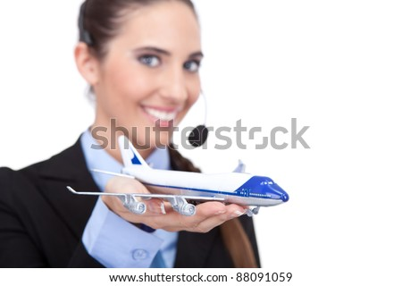happy woman stewardess holding jet aircraft in her arms on foreground, information about flying