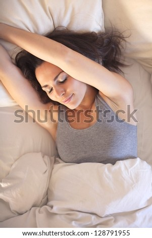 Happy woman stretching her arms while still lying on bed - stock photo