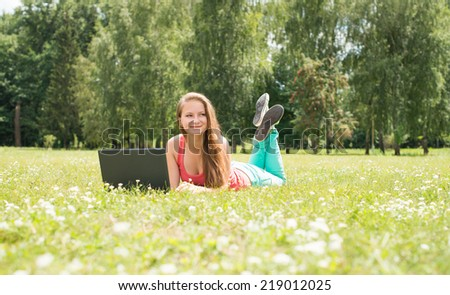 Happy woman student lying on grass with laptop. Successful girl online. Beautiful young woman with notebook in the park. Outdoor. Sunny day. Back to school. - stock photo