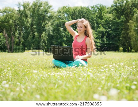 Happy woman student sitting on grass with laptop. Successful girl online. Beautiful young woman with notebook in the park. Outdoor. Sunny day. Back to school.