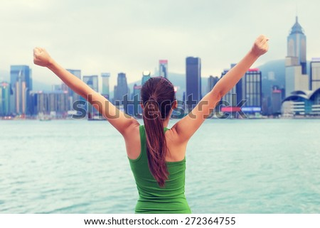Happy woman success cheering by Hong Kong skyline with arms raised up outstretched. Successful winner celebrating cheerful on Tsim Sha Tsui Promenade and Avenue of Stars in Victoria Harbour, Kowloon. - stock photo