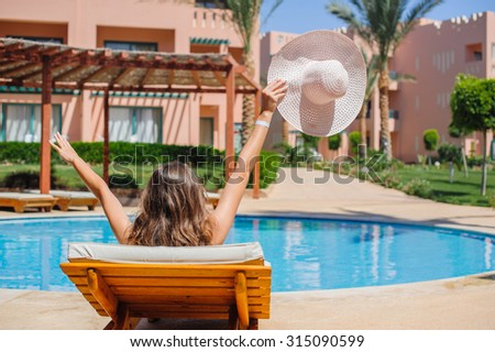 happy woman sunbathing on a lounger by the pool. - stock photo