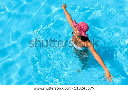 Happy woman swimming and dancing into pool on summer holidays. Brunette caucasian model playing into clear water on summer vacation. Copyspace. - stock photo