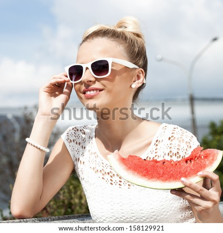 Happy woman takes watermelon from the opened fridge full of vegetables and fruit. Concept of healthy and dieting food - stock photo