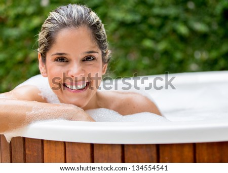 Happy woman taking a bath in the hot tub - stock photo