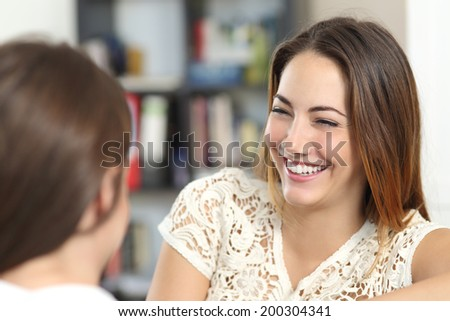 Happy woman taking a conversation and laughing with a friend at home            - stock photo