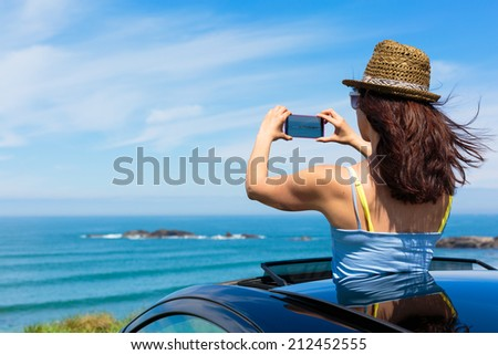 Happy woman taking photos to the sea with smartphone camera on car summer travel vacation to the coast. Brunette girl  leaning out vehicle sunroof towards the ocean. - stock photo