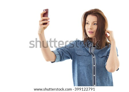 Happy woman taking selfie, isolated over white background - stock photo
