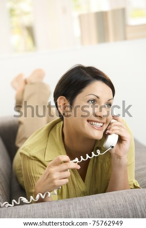Happy woman talking on landline phone, lying on sofa at home.