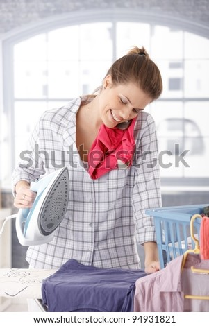 Happy woman talking on mobile phone while ironing clothes at home.? - stock photo