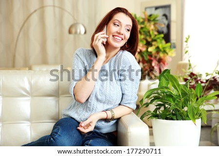 Happy woman talking on the phone and looking away at home - stock photo